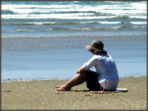 Woman Sits on Beach